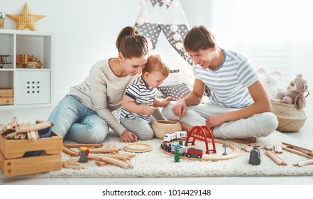 family mother father and baby son playing together in children's playroom
