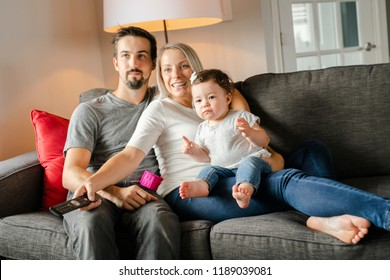 Family mother, father, child daughter at home watching tv