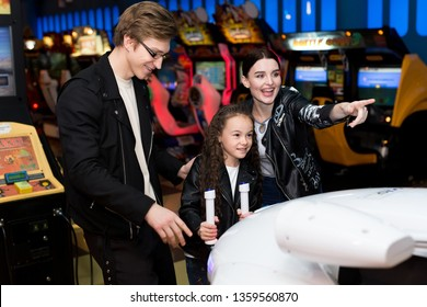 Family mother, father, daughter play arcade games on the computer machines at an amusement park. Children and adults play on the slot machines, attractions in the shopping center.
