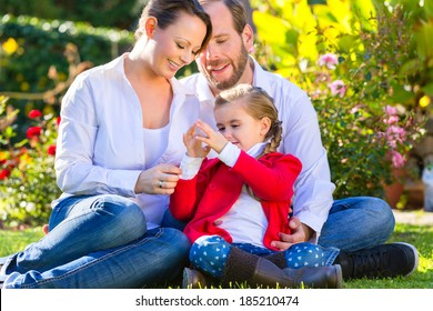 Family with mother, father and daughter together in the garden meadow