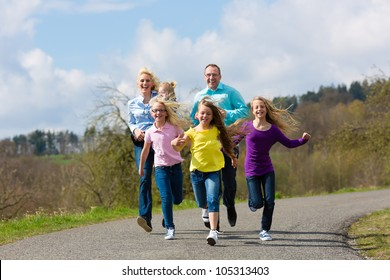 Family (mother, father and four children) is running outdoors in spring
