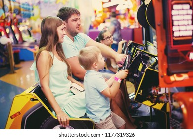 Family mother, father and little boy driving car arcade in game machine at an amusement park.