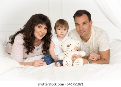 Family. Mother, father, little girl lying on the bed