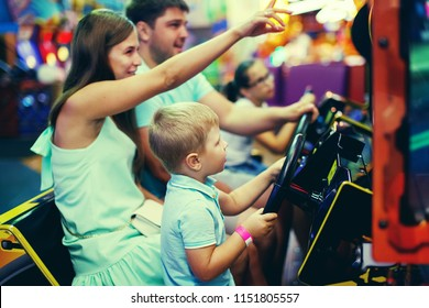 Family mother, father, teen girl with glasses and little boy driving car arcade in game machine at an amusement park. Selective focus.