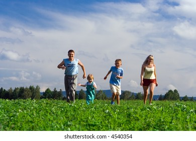 family mother father and two child run on field under blue sky