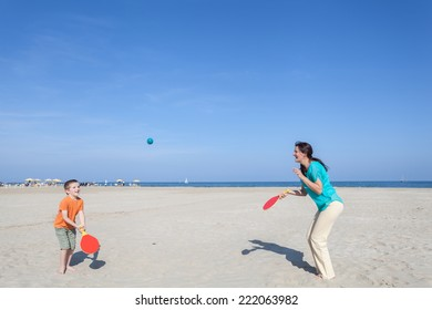 family mother and her son playing tennis on the beach