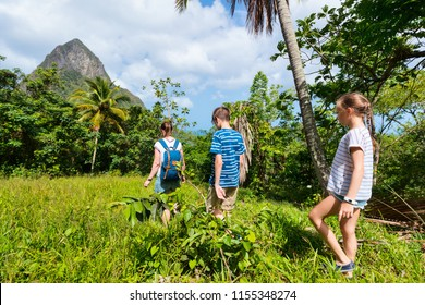 Family of mother and kids hiking on summer day at tropical island