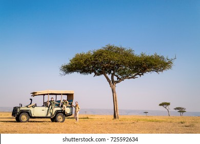 Family of mother and kids on African safari vacation enjoying morning game drive