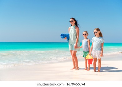 Family of mother and kids on summer vacation on white tropical beach