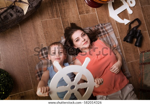 Family mother and the little son playing with vintage nautical things. Family  having fun at home. Travel and adventure concept.