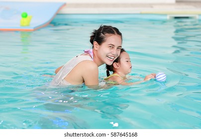 family of mother teaching kid in swimming pool