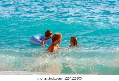 Family (mother with two children) have the water-based recreation on white Egremni beach (Ionian sea, Lefkada, Greece)