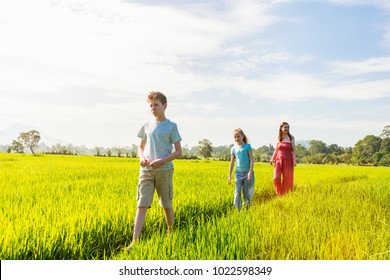 Family of mother and two kids enjoying peaceful walk in rice fields with breathtaking views over mountains in Sri Lanka