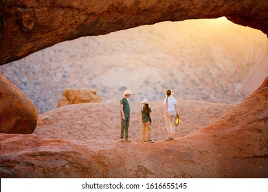 Family mother and two kids hiking in Spitzkoppe area with picturesque stone arches and unique rock formations in Damaraland Namibia