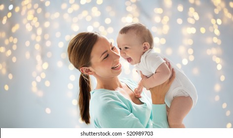 family, motherhood, child and parenthood concept - happy smiling young mother with little baby over holidays lights background