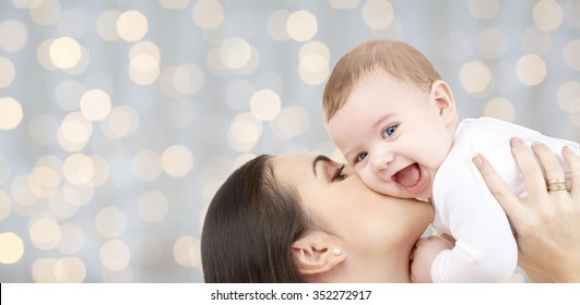 family, motherhood, children, parenthood and people concept - happy mother kissing her baby over holidays lights background