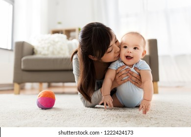 family and motherhood concept - happy smiling young asian mother kissing little baby at home