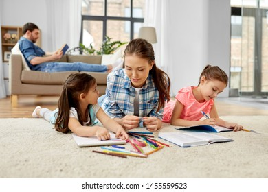 family, motherhood and leisure concept - mother spending time with her little daughters drawing and helping with homework lying on floor at home