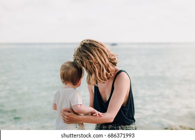 Family, motherhood, parenting, kids, babies concept. Sea, vacation. Mother hugging her baby daughter, delicate light tender portrait
