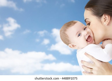 family, motherhood, parenting, people and child care concept - happy mother kissing adorable baby over blue sky background