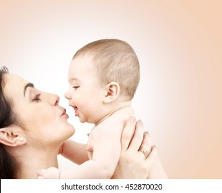 family, motherhood, parenting, people and child care concept - happy mother kissing adorable baby over beige background