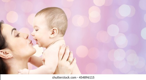family, motherhood, parenting, people and child care concept - happy mother kissing adorable baby over violet lights background