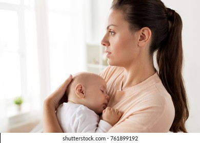 family, motherhood and people concept - close up of mother holding sleeping little baby boy at home