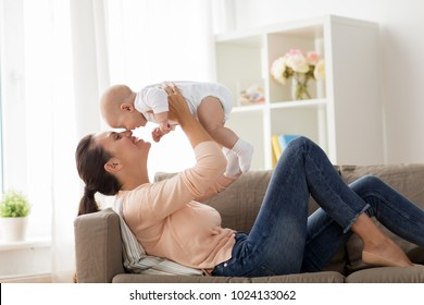 family, motherhood and people concept - happy mother with little baby boy lying on sofa at home