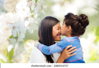 family, motherhood and people concept - happy mother and daughter hugging and kissing over cherry blossom background