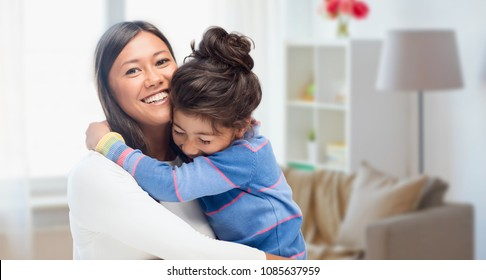 family, motherhood and people concept - happy mother and daughter hugging over over home room background