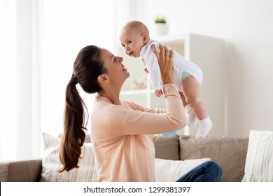 family, motherhood and people concept - happy mother playing with little baby boy at home