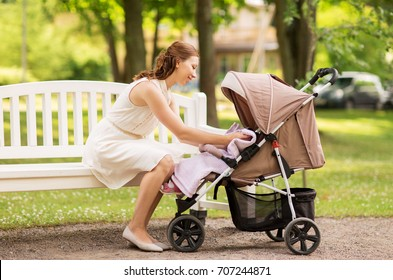 family, motherhood and people concept - happy mother with child in stroller at summer park