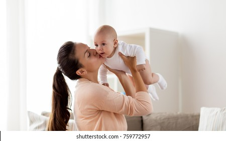 family, motherhood and people concept - happy mother kissing little baby boy at home