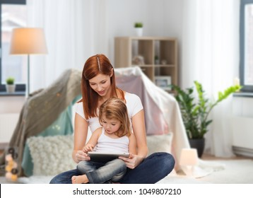 family, motherhood and technology concept - happy mother with adorable little daughter and tablet pc computer at home over kids room and tepee background