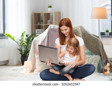 family, motherhood and technology concept - happy mother with adorable little daughter and laptop computer at home over kids room and tepee background