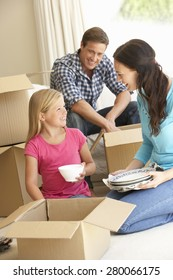 Family Moving Into New Home Surrounded By Packing Boxes