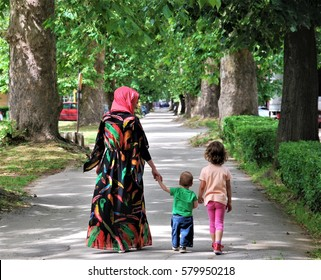 FAMILY: Muslim mother with her son and daughter; The promenade through the alley of plane trees in Maglaj, Bosnia and Herzegovina, June 2016.