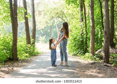 Family and nature concept - Mother with daughter walking in the green park