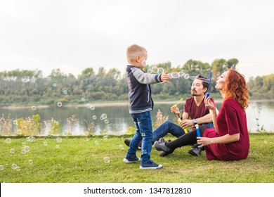 Family and nature concept - Mother, father and their child playing with colorful soap bubbles