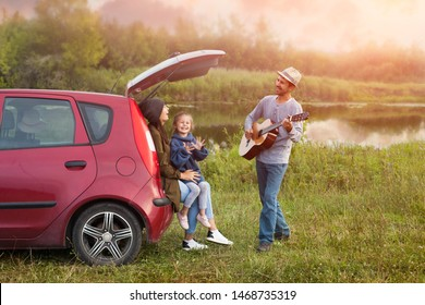 Family near the car outdoors and have fun. Happy mother and little daughter sit in the trunk, and father plays the guitar