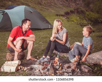 Family near the fire in the forest. Parent with child on a tent background