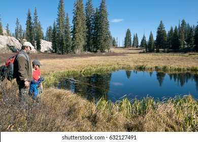 Family near a small round  Dog Lake and  coniferous forest,  Lake Mary Trail,  Uinta-Wasatch-Cache national forest. Utah, USA