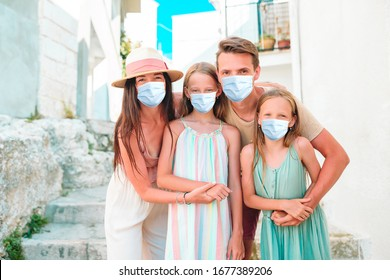 Family in old streets in Europ. Family portrait. Protection by Dangerous Coronavirus.