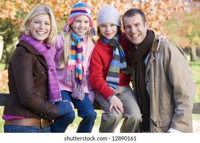 Family on autumn walk sitting on fence