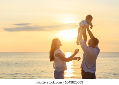 Family on the beach concept, Caucasian father playing and carrying his son on the tropical beach in sunset time with his wife