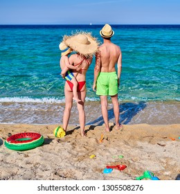 Family on beach with inflatable ring and toys. Young couple with three year old boy. Summer family vacation. Sithonia, Greece.