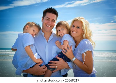 Family on a beach, standing, looking into camera.