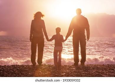 Family on the beach on sunset.