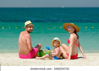 Family on beach. Two year old toddler boy playing with beach toys with mother and father on beach.