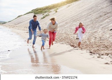 Family On Beach Vacation Running By Sea